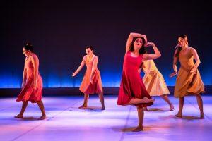 3 women in red dresses dancing on purple floor